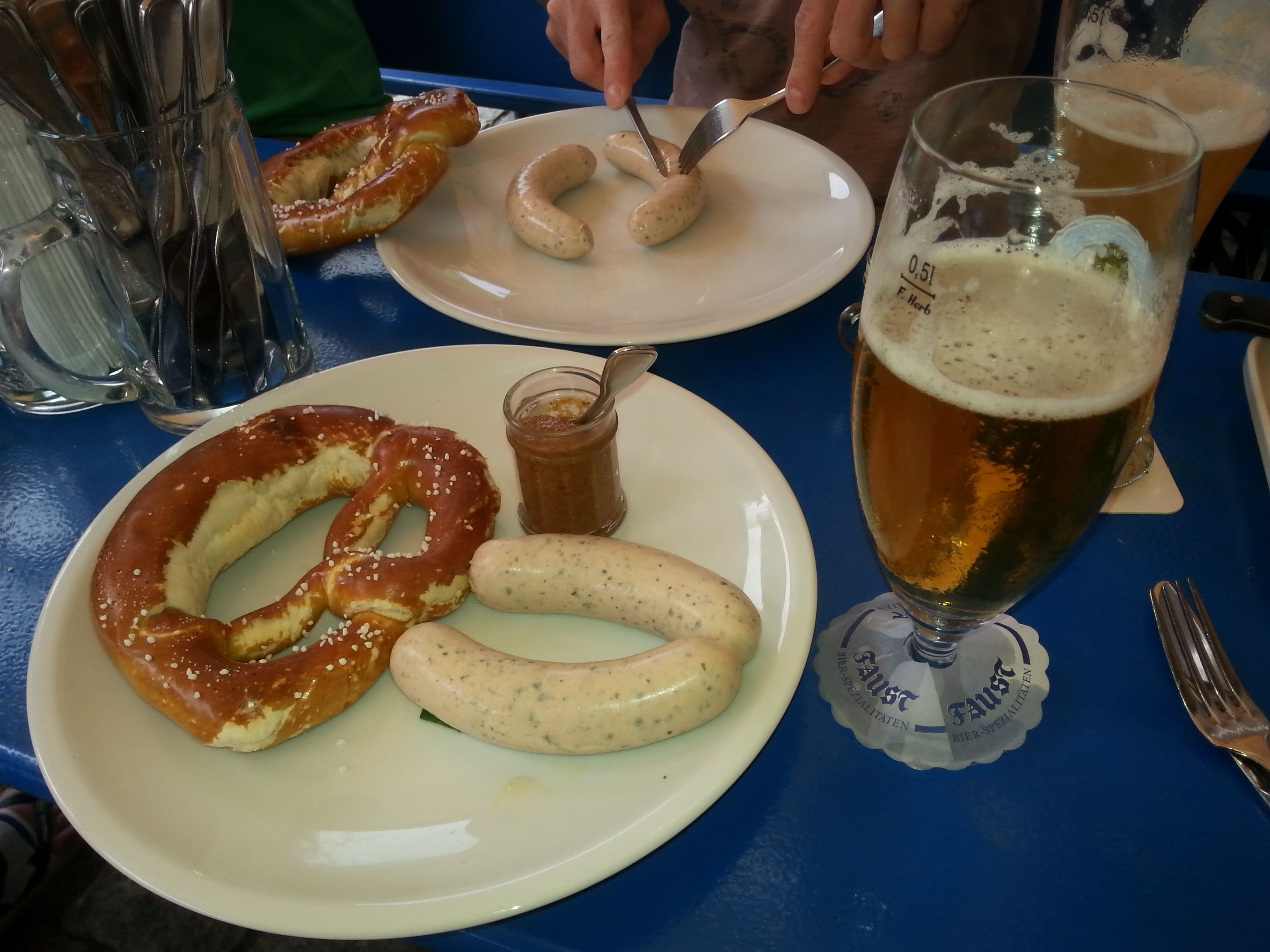 Traditional Bavarian breakfast: a pint of Weiss Beer, 2 Weiswurst (boiled) and a Brezn (a large pretzel) served with a sweet mustard on the side.